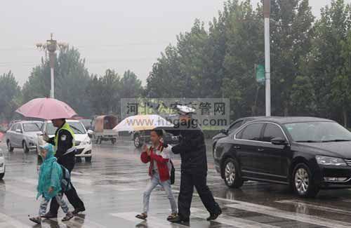 柏乡交警冒雨护校保安全