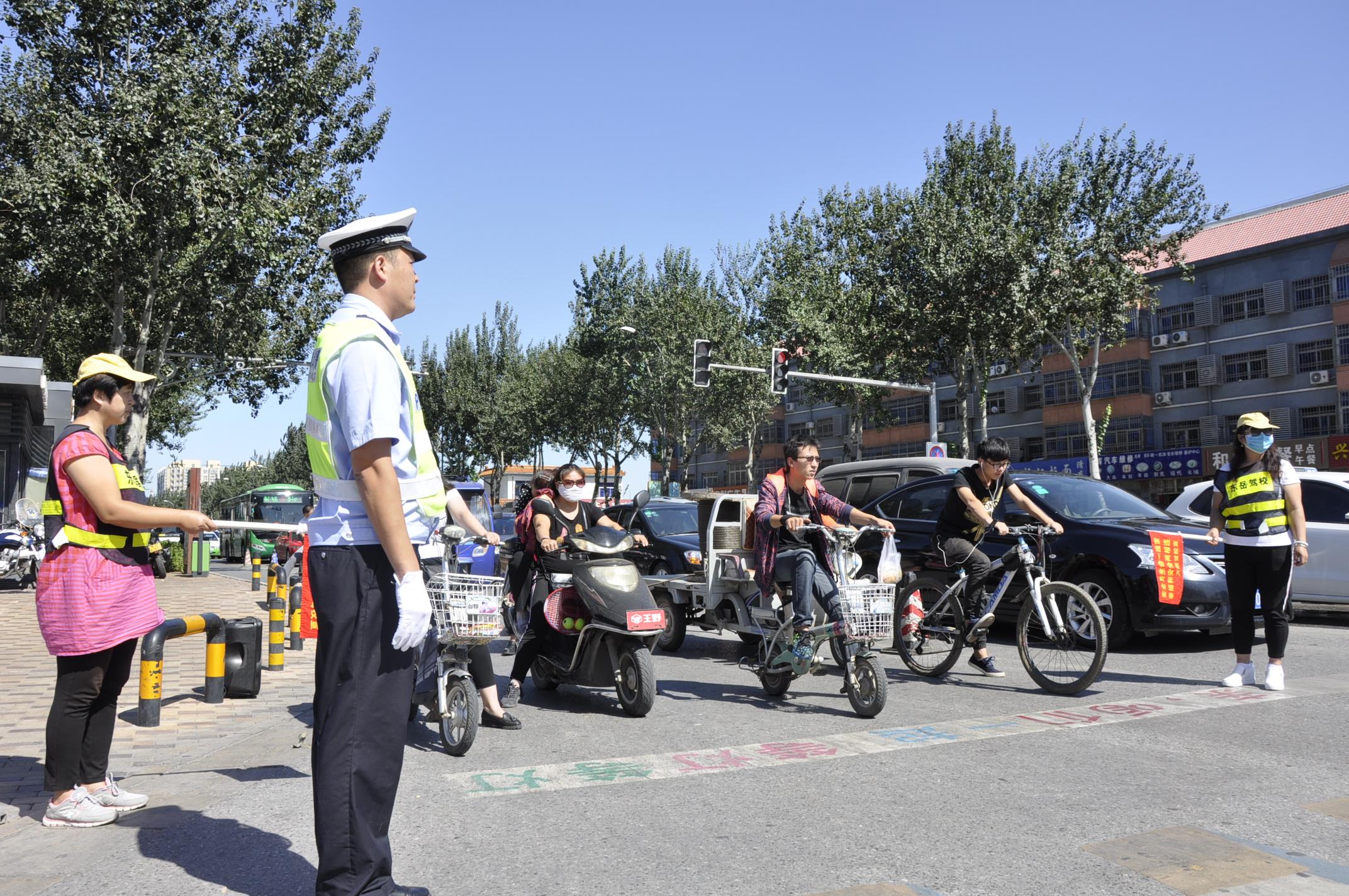 廊坊交警和志愿者并立街头管理  积极劝导过往群众安全出行