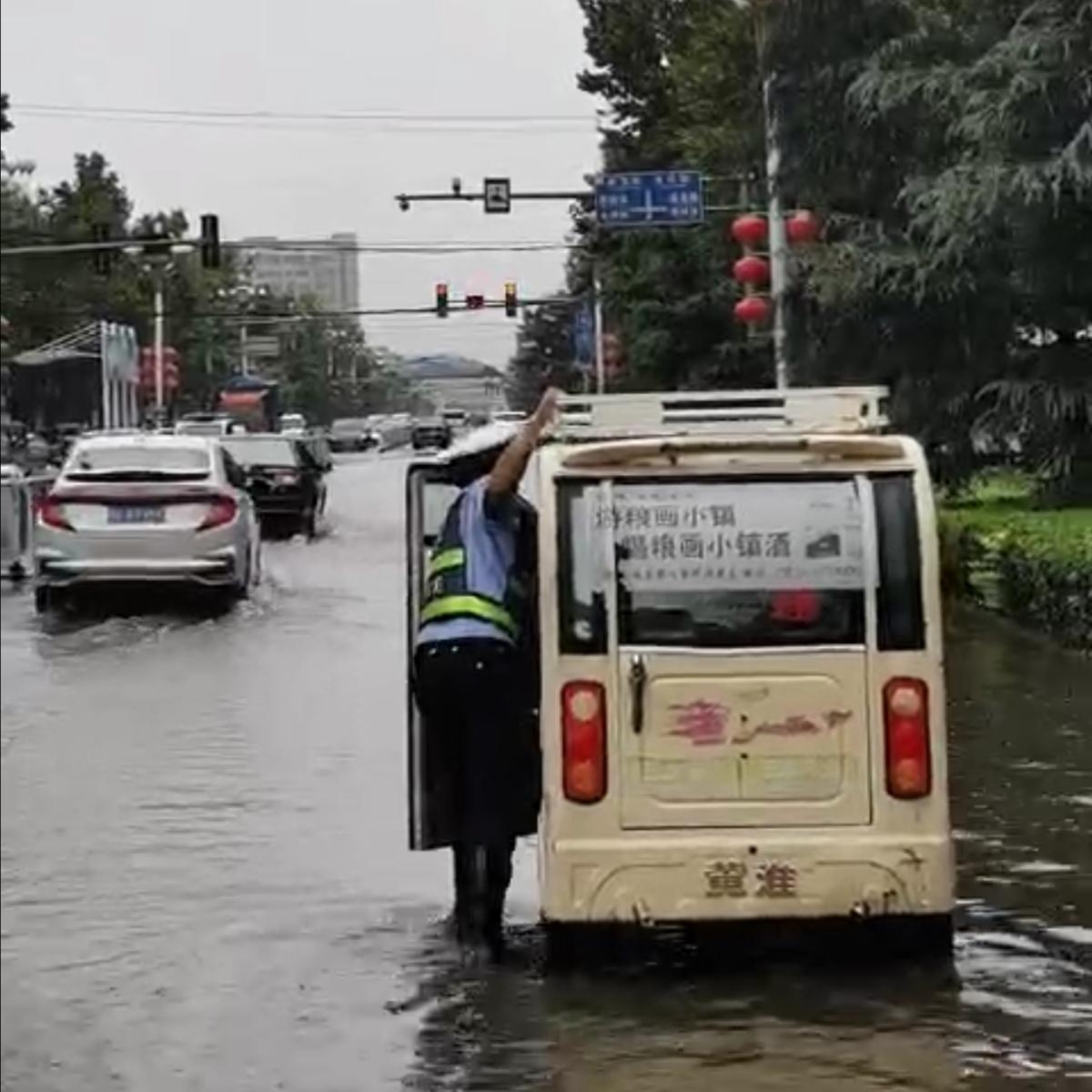 三轮车雨中抛锚 馆陶大队民警帮忙推车
